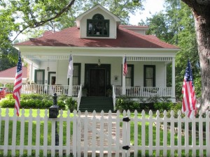 a house with a white picket fence and 4 american flags in the yard