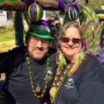 people dressed in purple, green and gold for mardi gras