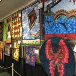 red, blue, brown and green quilted items hangin in the hallway