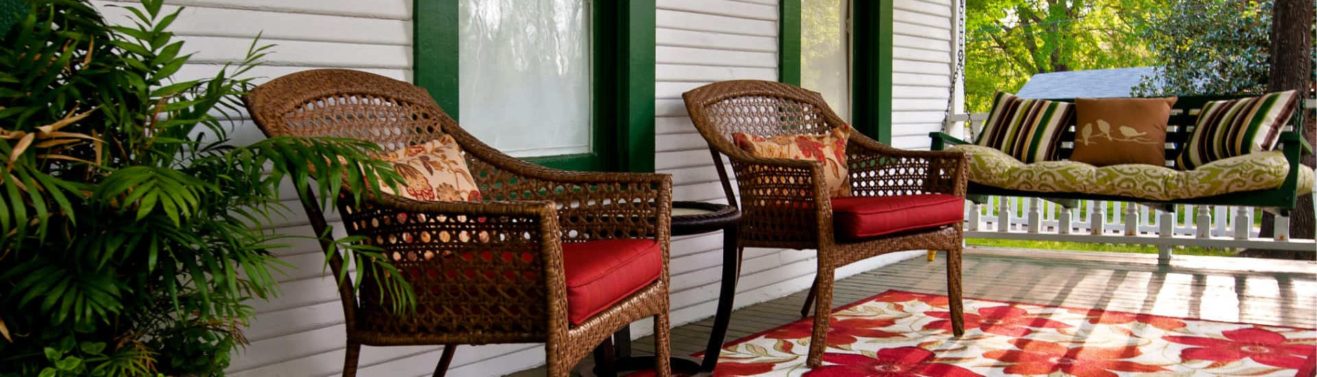 chairs on red flower rug and a porch swing