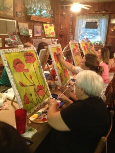 A group of women painting at the tables set up down the center of the restaurant.