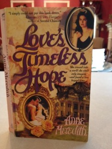 The cover of a romance novel by Anne Meredith. It has a picture of a large Greek revival home on it  and two oval pictures. One picture is of the novelist and the other is a man and woman in a loving embrace.