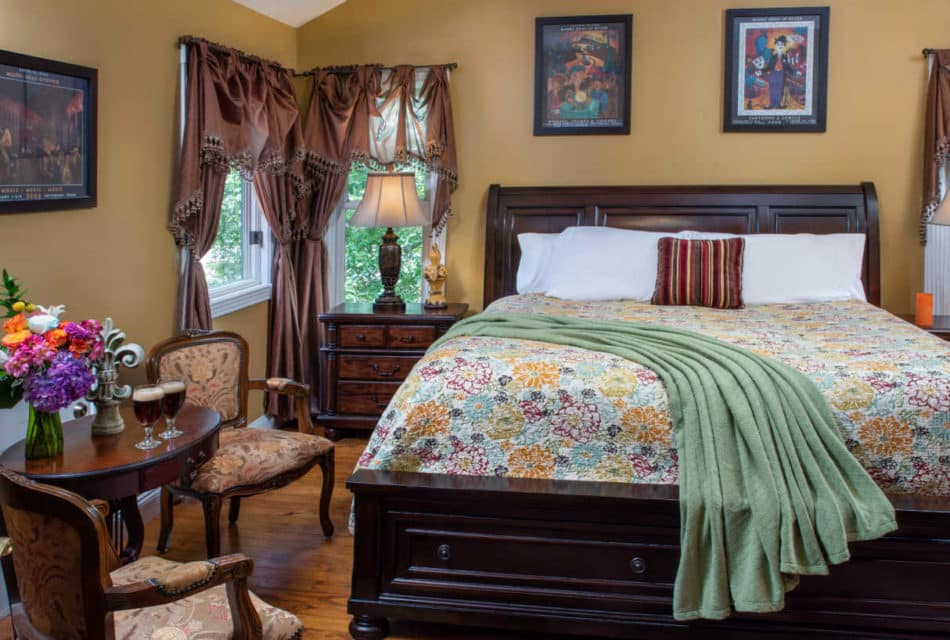 large high bed with yellow and green flowered spread in the front are 2 chairs next to a table