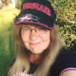 girl with blonde hair and a black and pink hat on