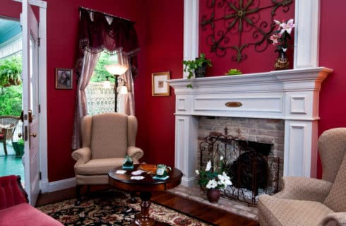 red room with a white fireplace and chairs