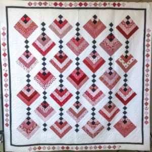 q white quilt with squares of red, pink,rose and black colors in rows.