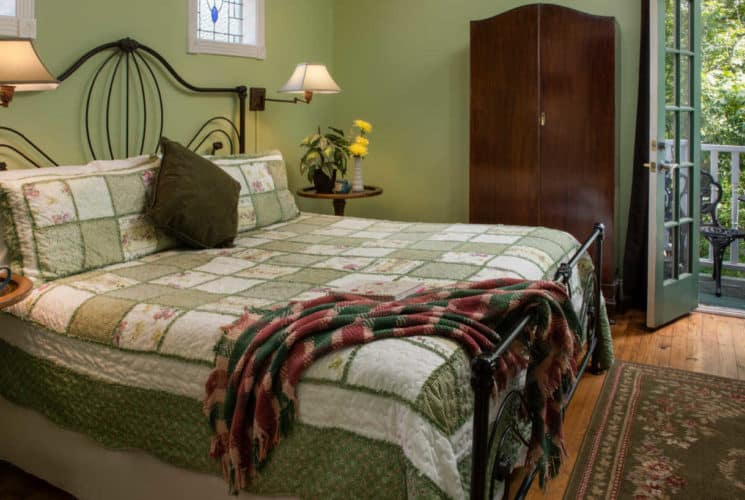 large bed with green and white spread in front of a wooden cupboard