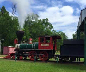 red steam train with a green boiler on a bright blue day