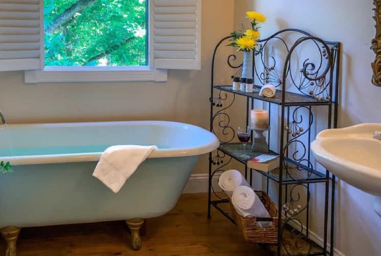 claw foot tub with a white towel below a window