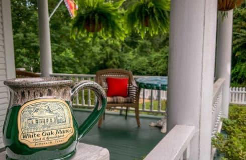 green mug sitting on a white railing
