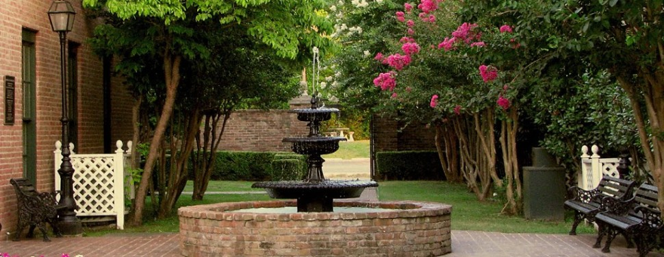 black and brick fountain under trees with pink flowers
