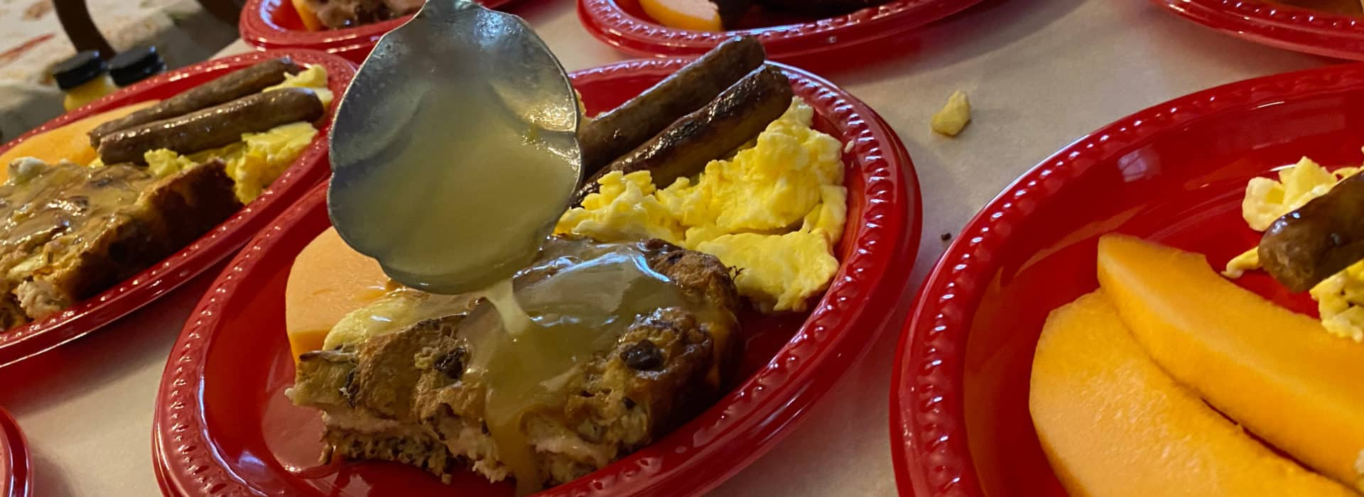 red plate with eggs sausage bread pudding with a spoon pouring sauce over it