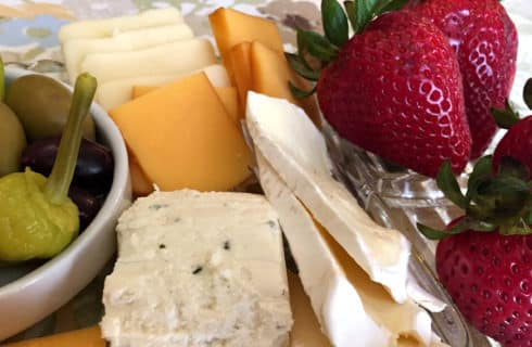 white and orange cheese slices, a bowl of green peppers and strawberries