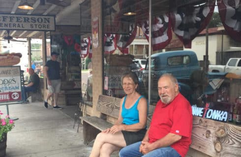 man and women sitting on a bench in front of a store
