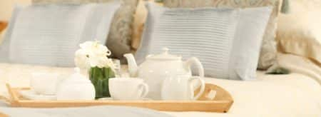 Wooden tray with white tea set on top of bed