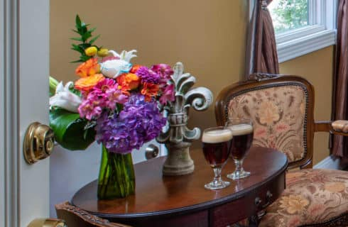 wodden table with a bouquet of flowers and beer glasses on it