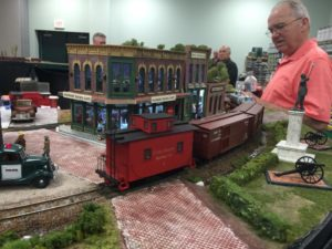a model scale red caboose traveling down the track