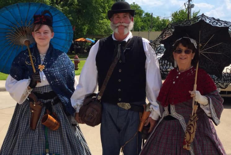 2 ladies and a man dressed in historic outfits walking in the street