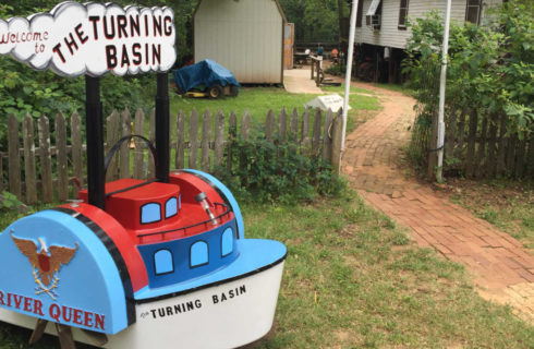a red, white and blue boat shaped sign