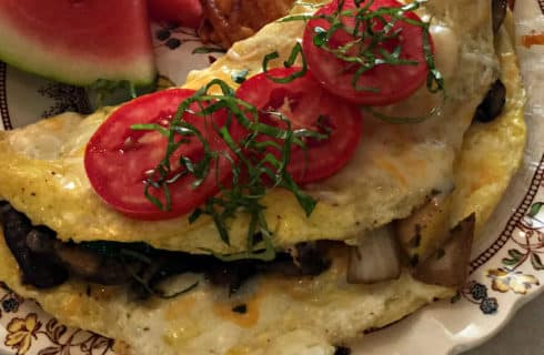 vegetable omelete with tomato slices and basic slivers