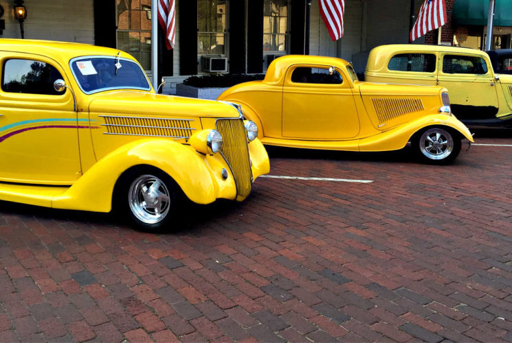 3 old cars painted in bright yellow on the red brick streets